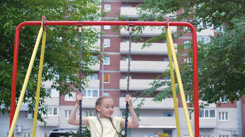 Carefree teenager girl swinging on playground in residential area on brick house Live Action