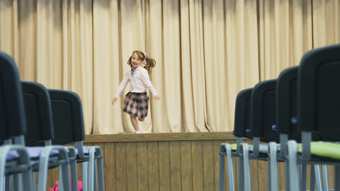 Little girl on stage in a hall without people. the girl revolves around herself Live Action