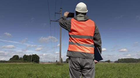Electrician take pictures under high-voltage lines Footage