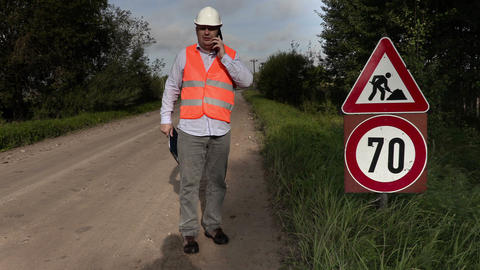 Engineer near to the road signs of road repairing Footage