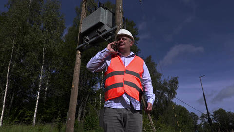 Electrician talking on the phone near high-voltage lines and transformer Footage