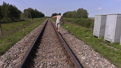 Teen walking away and trying to balance on rails Footage