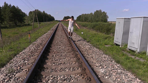 Teen walking and trying to balance on rails Footage