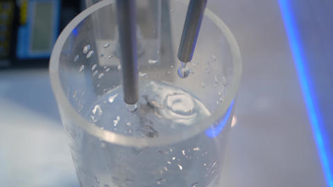 Slow motion: droplets falling from tube - compact liquid dosing system: close up Live Action
