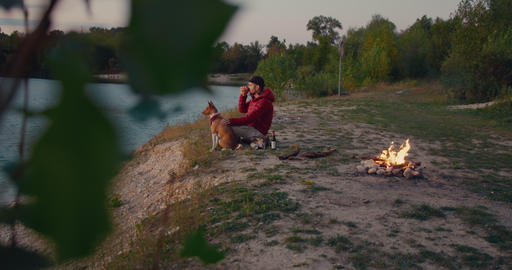 Man and pet dog rest next to campfire on hike trip Live Action