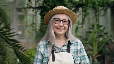 Likable cheerful grey-haired 65-70-aged female gardener in hat and working Live Action