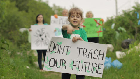 Girl volunteer holds protesting poster Don't Trash Our Future. Plastic nature Live Action