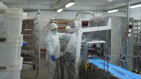Worker of the sausage department is standing near the automatic device for ライブ動画