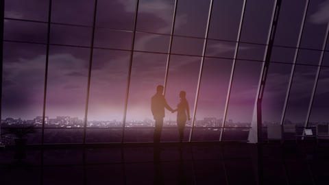 Silhouettes of a businessman and a business woman shaking hands Fotografía