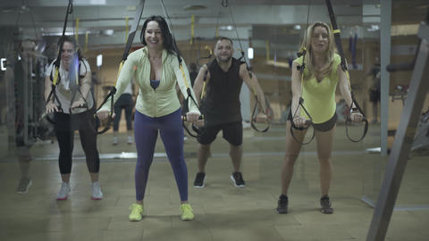 Four joyful athletic people training in gym and smiling. Portrait of Caucasian Live Action