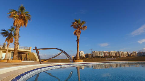Malta, Luxury Mediterranean vacation concept. Pool, palms and cityscape Live Action