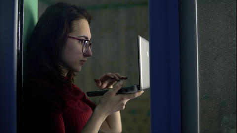 A young woman is sitting at home with a laptop in her hands. A girl sits on a Live Action