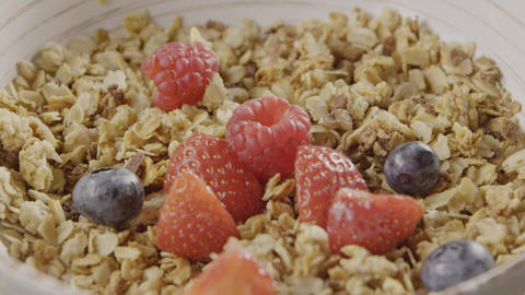Cooking of healthy breakfast from falling granola, fresh organic Live Action