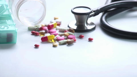Top view of colorful pills spilling on white background Live Action