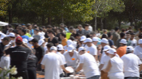 People In White Give Food At Event Footage