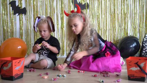 Little boy and blond curly hair girl have fun on Halloween party at home Live Action