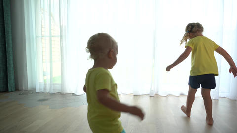 Little Girl and Young Adorable Boy Have Fun Spin around at Home Live Action