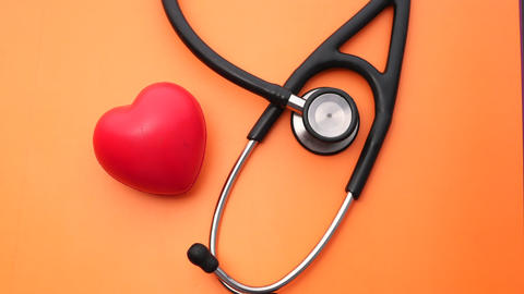 heart shape symbol and stethoscope on orange background Live Action