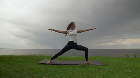 Young fit woman practice yoga on coast near the lake or sea. Woman doing Warrior Live Action