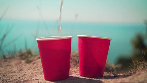 Two red disposable cups of tea on the background of the sea and the horizon Live Action