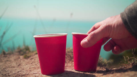 Two red disposable cups of tea or coffee against the background of the sea and Live Action