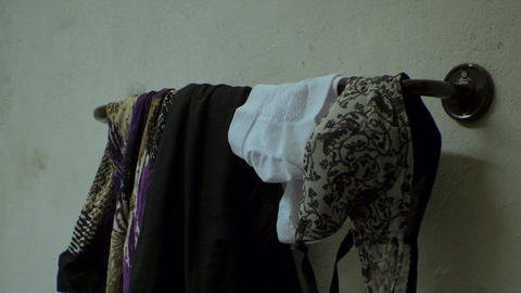 Close up clothes, woman clothes on hanging rack in bathroom Live Action