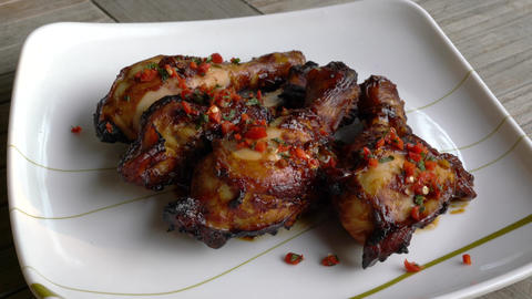Baked honey chicken drumsticks with basil leaves and cut chilly Live Action