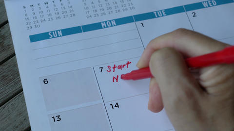 Woman writing down the words, start new job with red pen on calendar Live Action