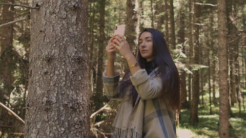 woman recording vlog video on phone outdoors in forest Live Action