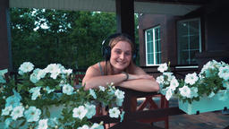 A beautiful, young girl with headphones on a beautiful veranda decorated with flowers listens to Live Action