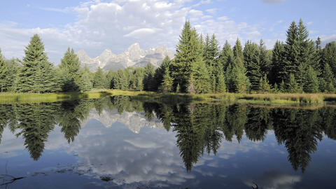 Time lapse of clouds, mountains and forest reflecting at Schwabacher Landing in Grand Teton National Footage
