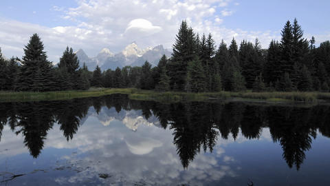 Time lapse of clouds, mountains and forest reflecting at... Stock Video Footage