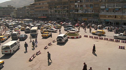 A wide establishing shot of downtown Kabul, Afghanistan with bus, taxi and vehicle traffic Footage