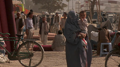 Slow mo shot of a woman in burka walking with her child in Kabul, Afghanistan Footage