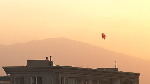 Family flying kites from a rooftop in Kabul, Afghanistan Stock Video Footage