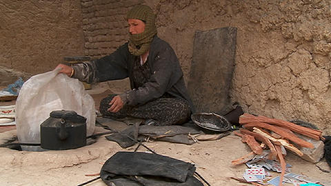 A woman puts wood into a tandor oven in Kabul, Afghanistan Footage