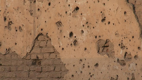 Tilt up of bullet holes in a wall in Kabul, Afghanistan Stock Video Footage
