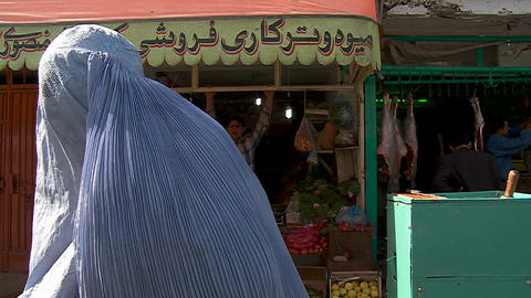 Woman in burqa begging in front of shops in Kabul, Afghanistan Footage