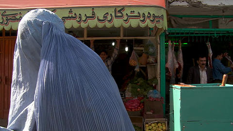Woman in burqa begging in front of shops in Kabul,... Stock Video Footage