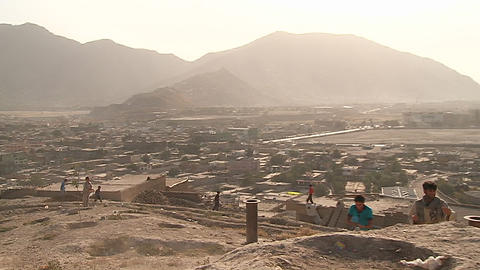 Boys play on the hillsides flying kites in modern Kabul, Afghanistan Footage