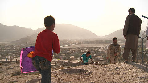 Boys play on the hillsides flying kites in modern Kabul,... Stock Video Footage