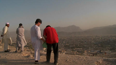 Men fly kites on a hill overlooking Kabul, Afghanistan Stock Video Footage