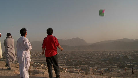 Men fly kites on a hill overlooking Kabul, Afghanistan Footage