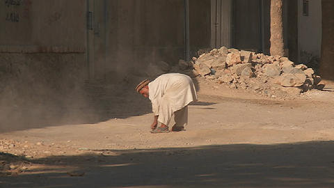 An old man sweeps the street and clears stones and rocks in Kabul, Afghanistan Footage