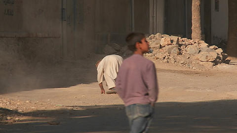 An old man sweeps the street and clears stones and rocks... Stock Video Footage