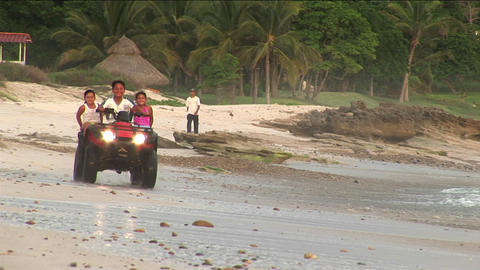 A man and two children ride an ATV through the water on a... Stock Video Footage