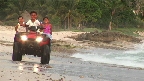 A man and two children ride an ATV through the water on a beach Footage