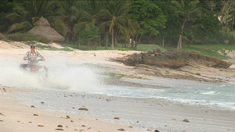 A man rides an ATV through the water on the beach Stock Video Footage