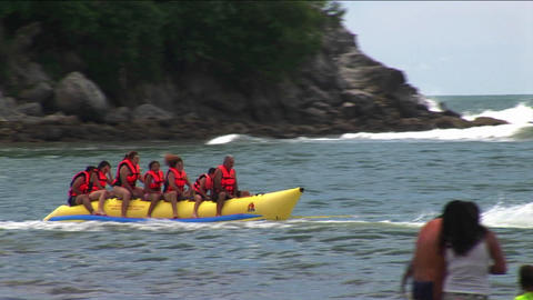 A group of young people wearing red life jackets ride through the water on a yellow boat Footage