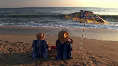 A couple under an umbrella on the beach make a toast and share a kiss Footage